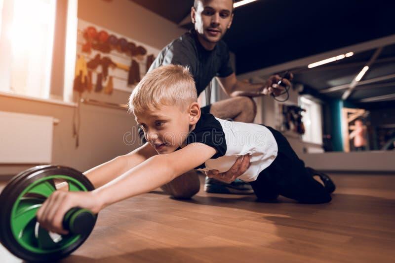 Vader en zoon in de gymnastiek De vader en de zoon brengen samen tijd door en leiden een gezonde levensstijl stock afbeelding