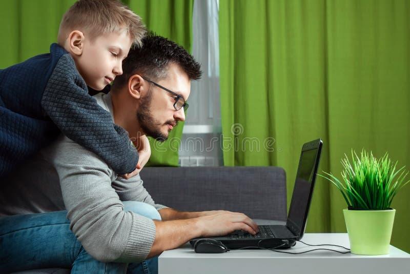 Vader en zoon die aan laptop werken Zakenman die van huis werken en voor een kind zorgen, die tijd met een kind doorbrengen E stock afbeelding
