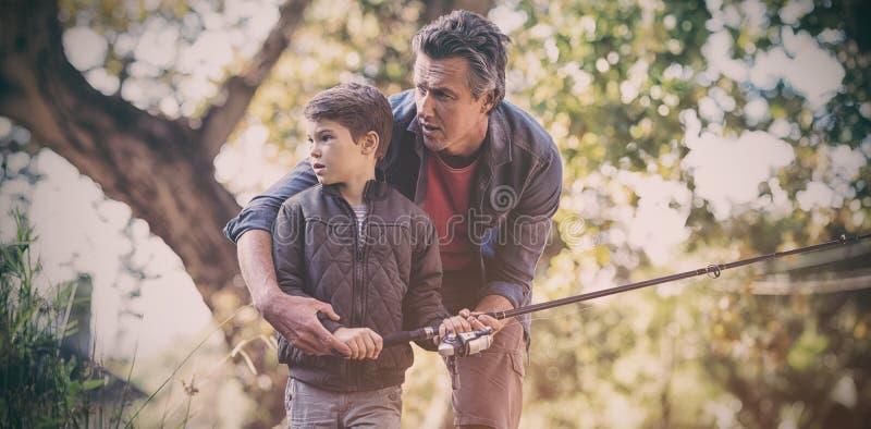 Vader en zoon die in bos vissen royalty-vrije stock foto's