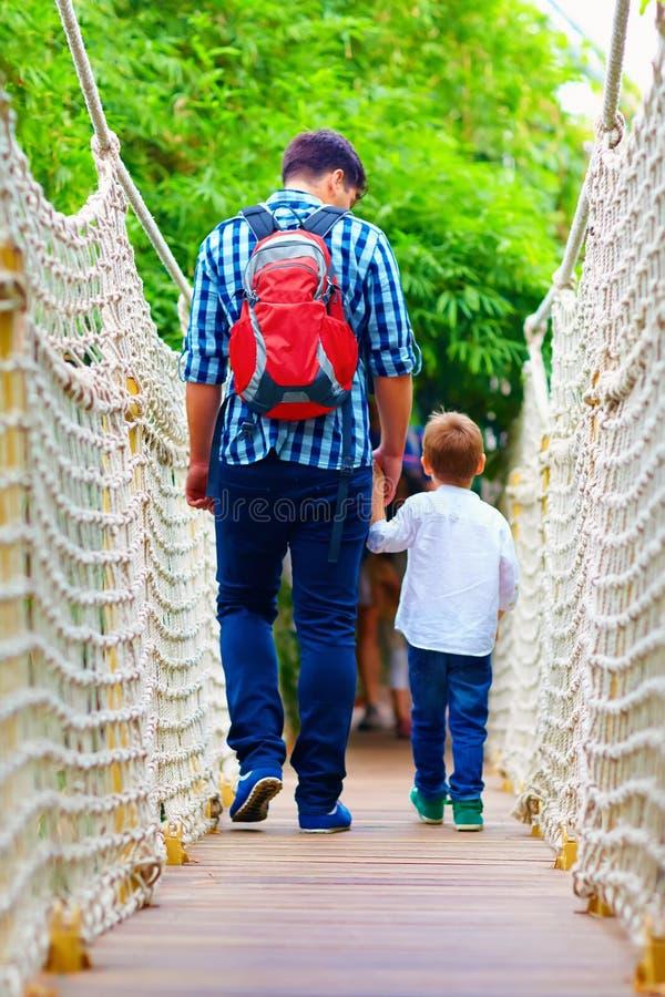 Vader en zoon die door hangbrug reizen royalty-vrije stock foto