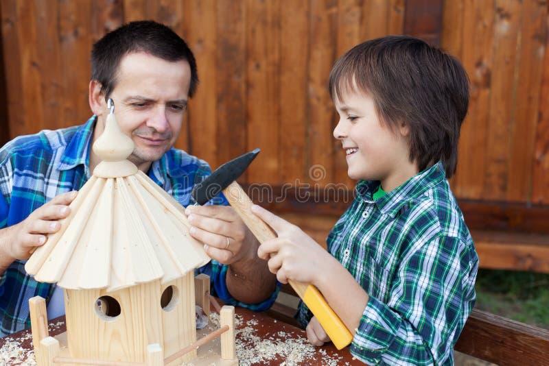 Vader en zoon die een een vogelhuis of voeder bouwen stock fotografie