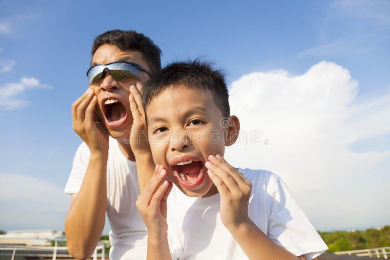 Vader en zoon die een grimas samen in het park maken stock afbeeldingen