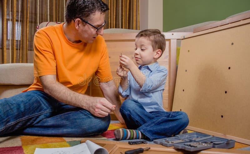 Vader en zoon die een nieuw meubilair voor huis assembleren stock fotografie