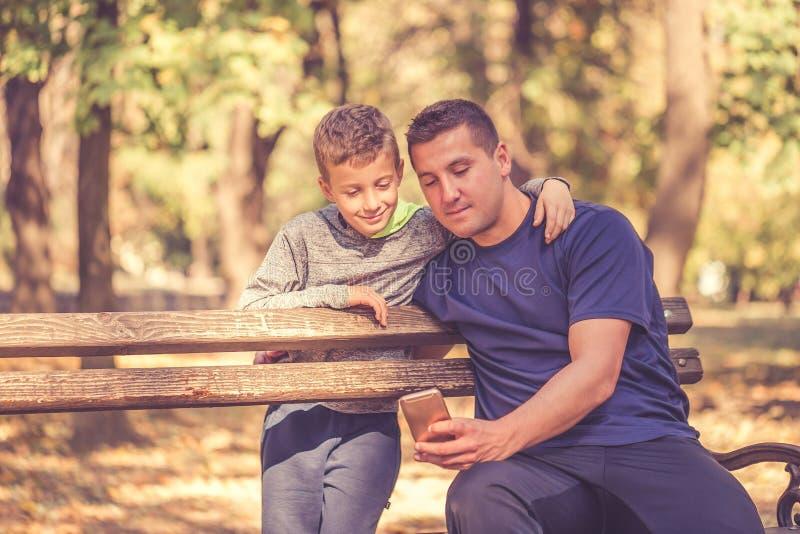 Vader en zoon die een onderbreking na training nemen en op iets op smartphone in het park letten stock foto