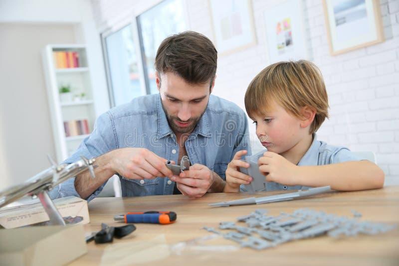 Vader en zoon die een vliegtuigstuk speelgoed construeren stock foto's