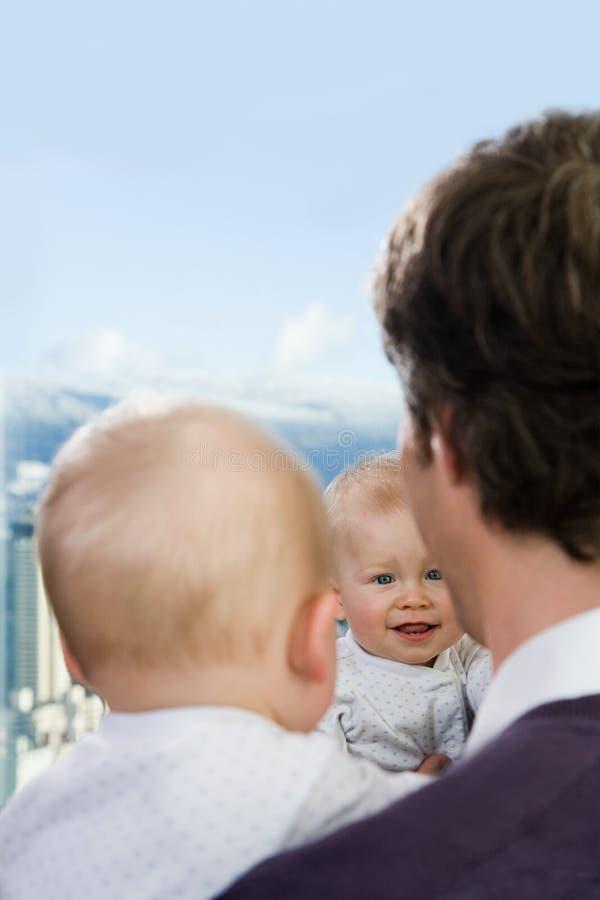 Vader en zoon die hun gedachtengang in een venster bekijken stock fotografie