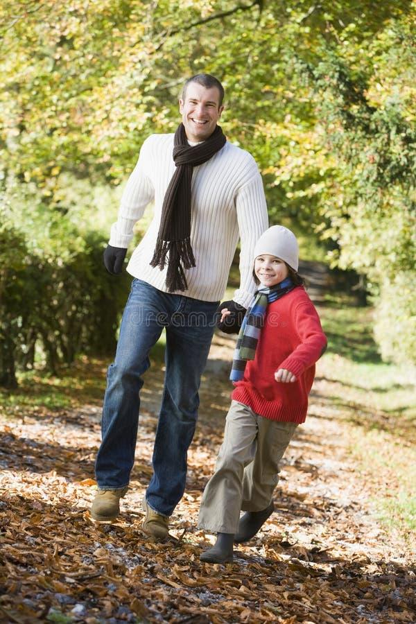 Vader en zoon die langs de herfstweg lopen royalty-vrije stock afbeeldingen