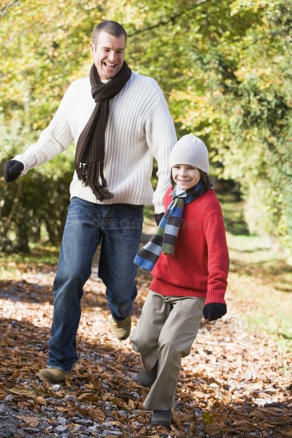 Vader en zoon die langs de herfstweg lopen stock fotografie