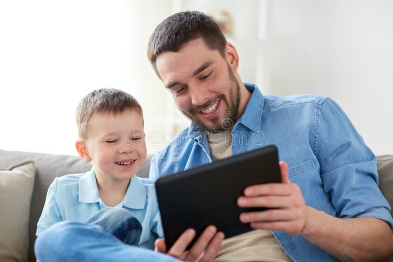Vader en zoon die met tabletpc thuis spelen stock foto