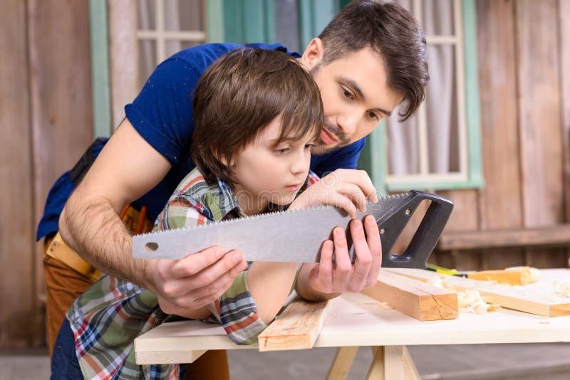 Vader en zoon die op houten lijst en het inspecteren handzaag leunen stock foto's