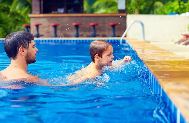 Vader en zoon die in pool bij de zomervakantie zwemmen royalty-vrije stock fotografie