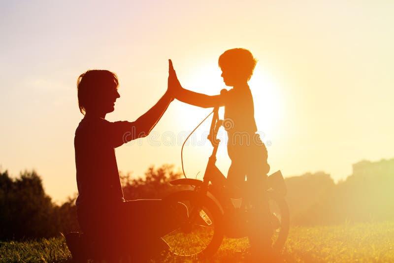 Vader en zoon die pret berijdende fiets hebben bij zonsondergang royalty-vrije stock foto's