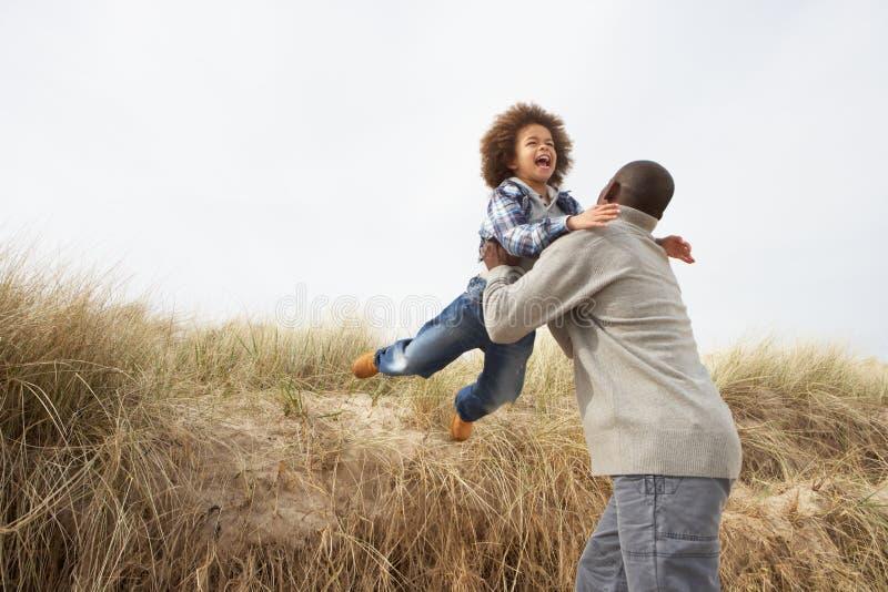 Vader en Zoon die Pret in de Duinen van het Zand hebben royalty-vrije stock fotografie