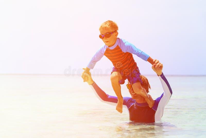 Vader en zoon die pret hebben op zee stock foto's
