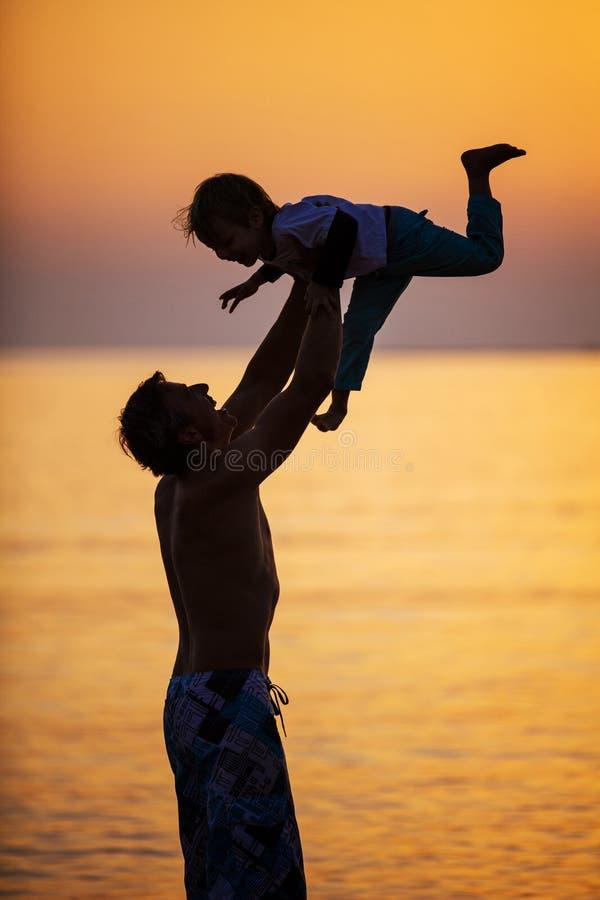 Vader en zoon die pret op strand hebben bij zonsondergang stock fotografie