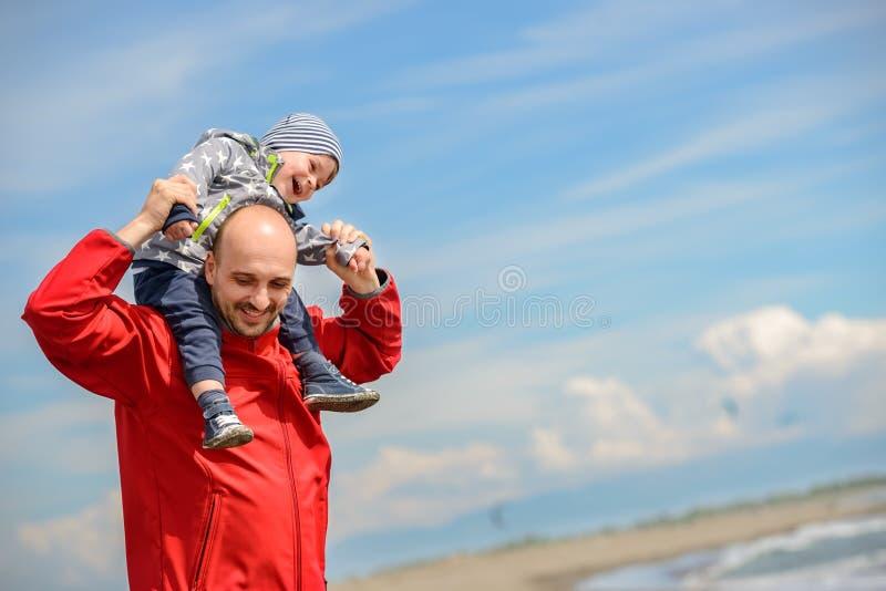Vader en zoon die pret op tropisch strand hebben stock afbeelding