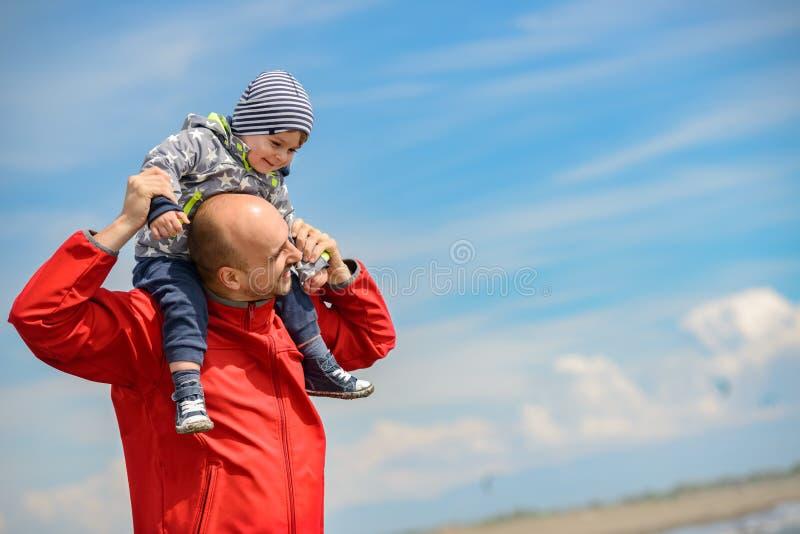 Vader en zoon die pret op tropisch strand hebben royalty-vrije stock afbeelding