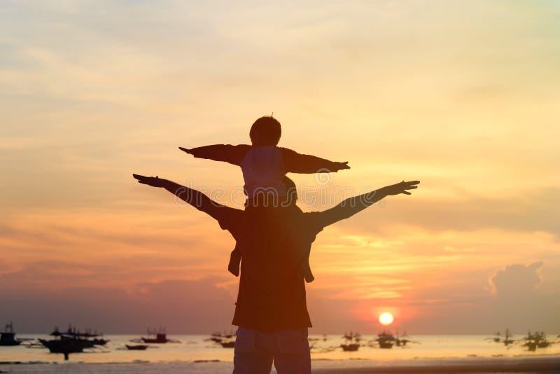 Vader en zoon die pret op zonsondergangstrand hebben stock foto