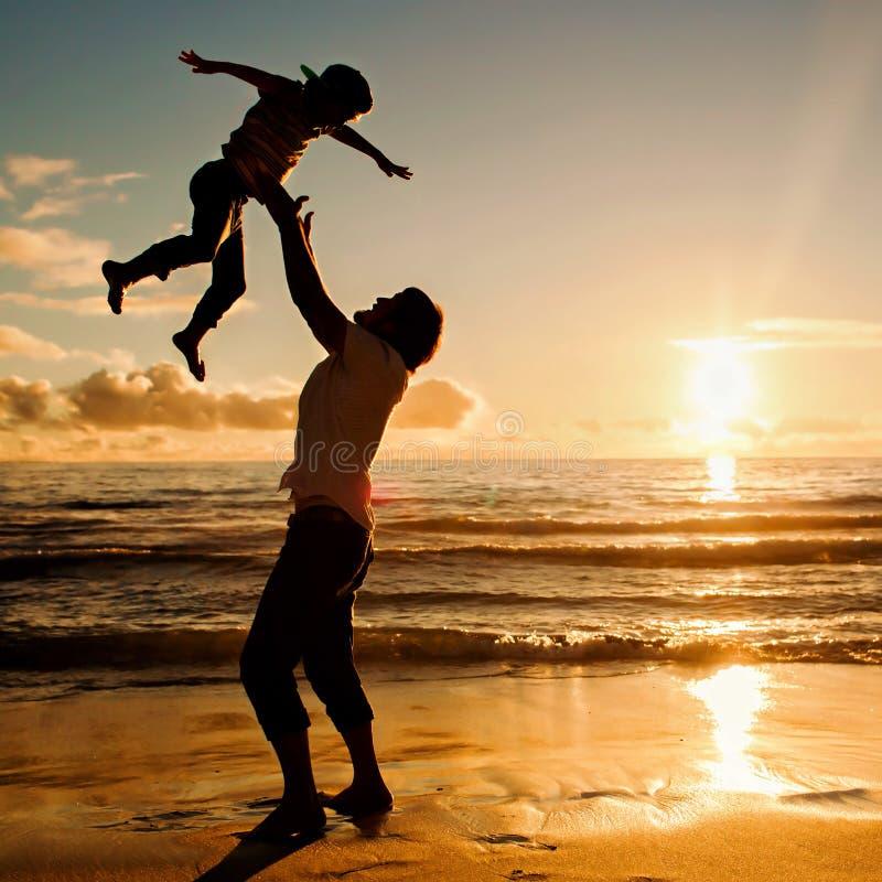 Vader en zoon die pret samen in zonsondergangoceaan hebben stock foto's