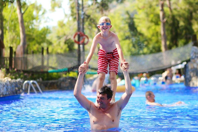 Vader en zoon die pret in zwembad hebben stock foto