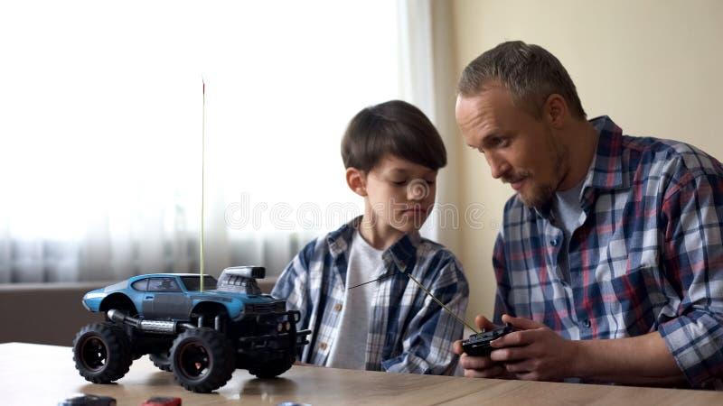 Vader en zoon die radio-gecontroleerde auto, vrije tijdsactiviteit, verjaardagsgift in werking stellen stock foto