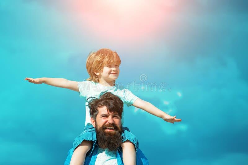 Vader en zoon die samen spelen Het kind zit op de schouders van zijn vader Familietijd royalty-vrije stock afbeelding