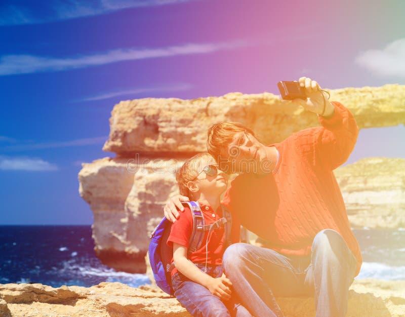 Vader en zoon die selfie foto maken tegen Azuurblauw stock foto
