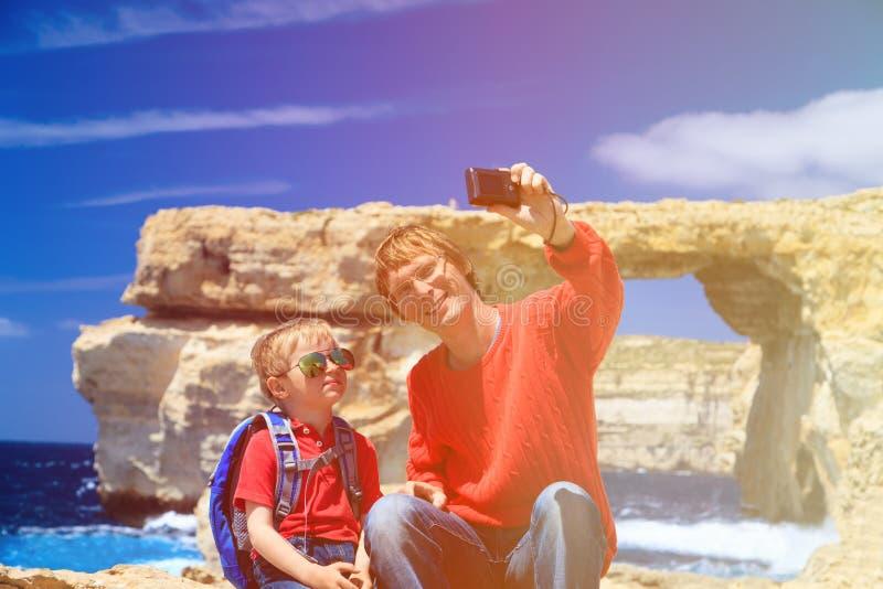 Vader en zoon die selfie tegen Azure Window maken stock fotografie