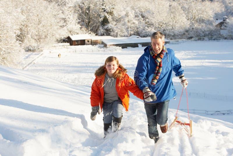 Vader en Zoon die SneeuwHeuvel van de Slee trekken de omhoog