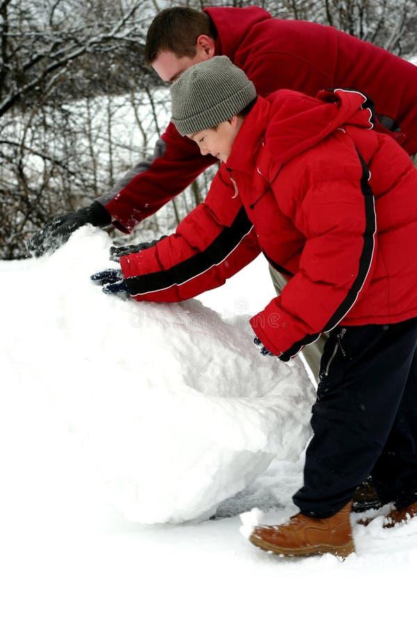 Vader En Zoon Die Sneeuwman Maken Stock Afbeeldingen