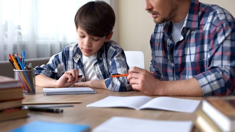 Vader en zoon die thuiswerk doen samen, papa die taak, schoolonderwijs verklaren stock afbeelding