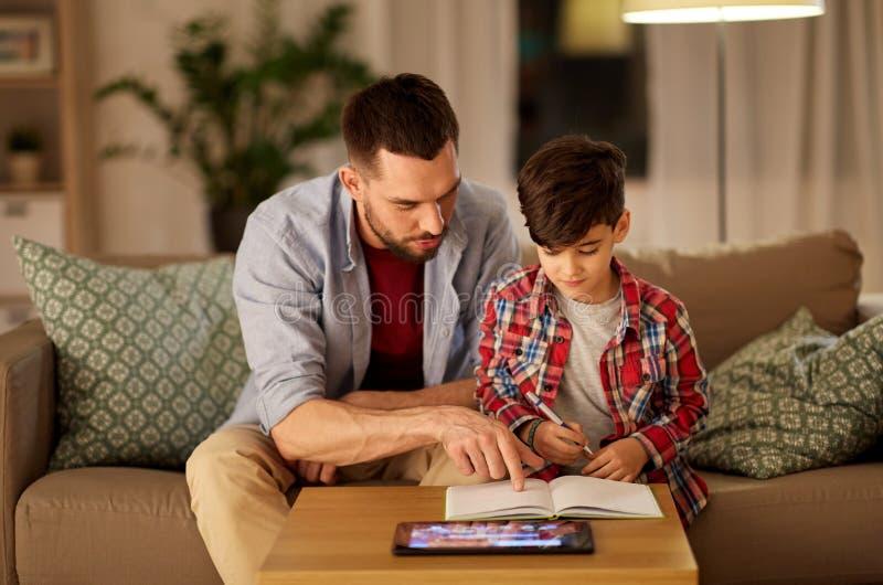Vader en zoon die thuiswerk samen doen royalty-vrije stock fotografie