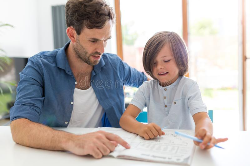 Vader en zoon die thuiswerk samen doen royalty-vrije stock afbeeldingen