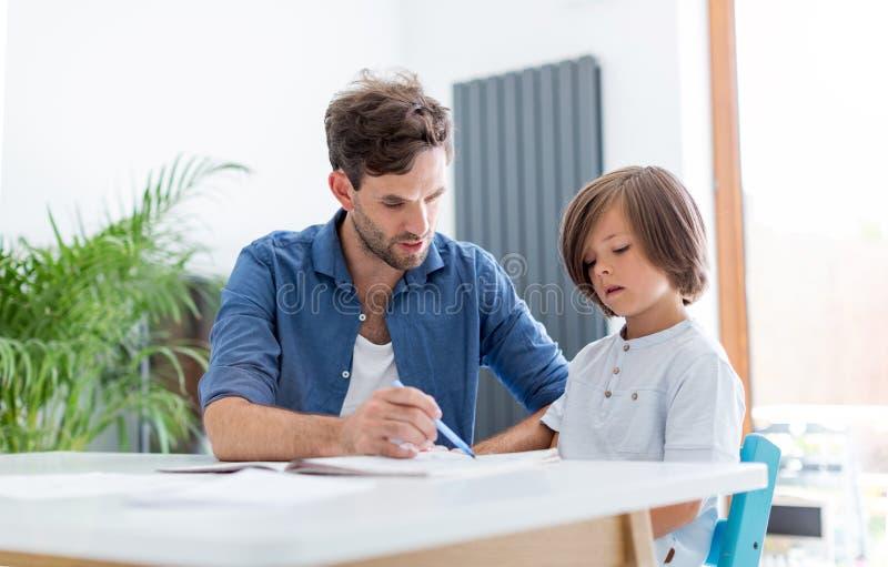 Vader en zoon die thuiswerk samen doen stock foto