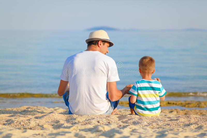 Vader en zoon die van tijd genieten bij het strand royalty-vrije stock afbeeldingen