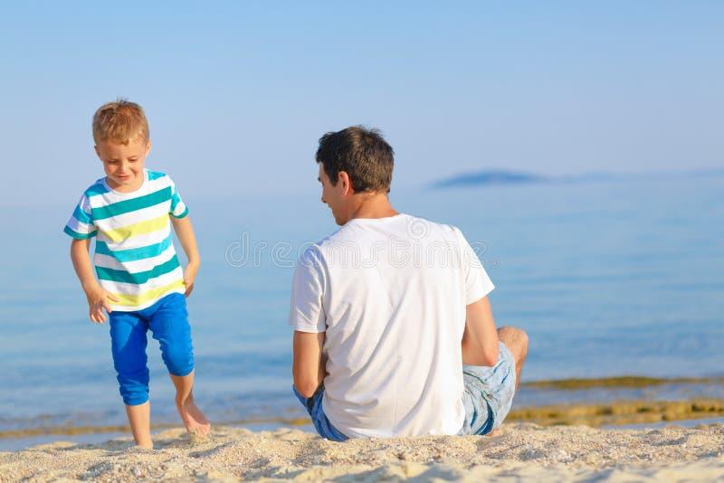 Vader en zoon die van tijd genieten bij het strand stock foto
