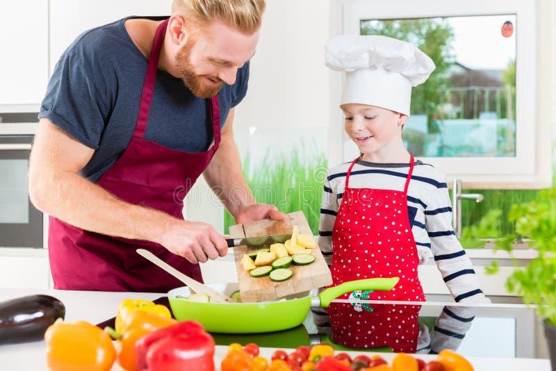Vader en zoon die voedsel samen in keuken voorbereiden stock afbeelding