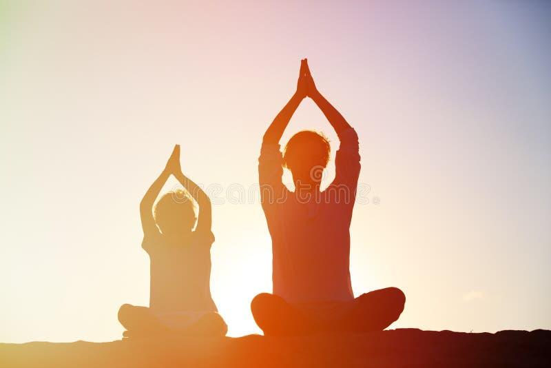 Vader en zoon die yoga doen bij zonsonderganghemel stock foto's