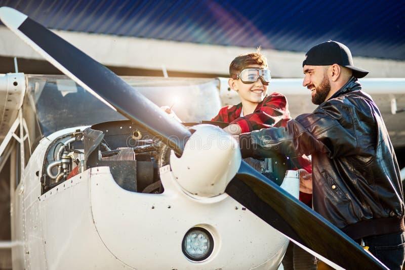 Vader en zoon die zich boven geopend motorkabinet bevinden, die vliegtuig controleren vóór vlucht stock fotografie