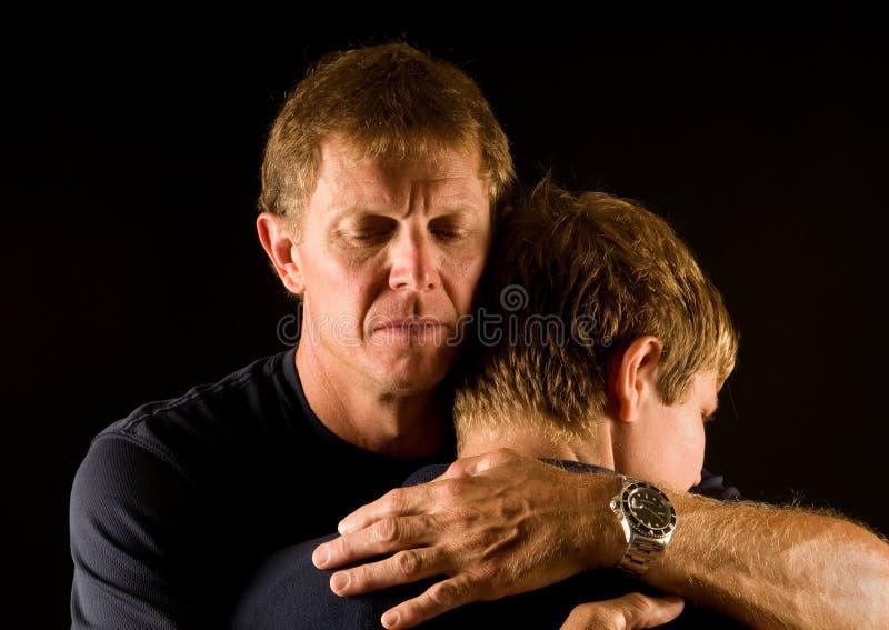 Vader en zoon in emotionele omhelzing stock fotografie