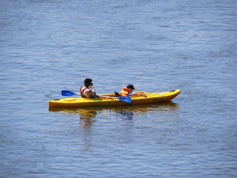 Vader en zoon Kayaking op MRiver bij Zon stock foto's