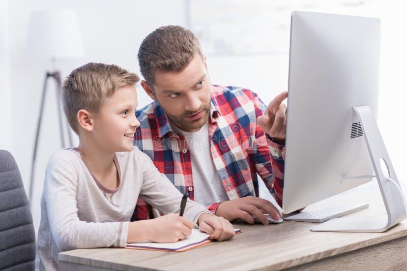 Vader en zoon met bureaucomputer stock foto