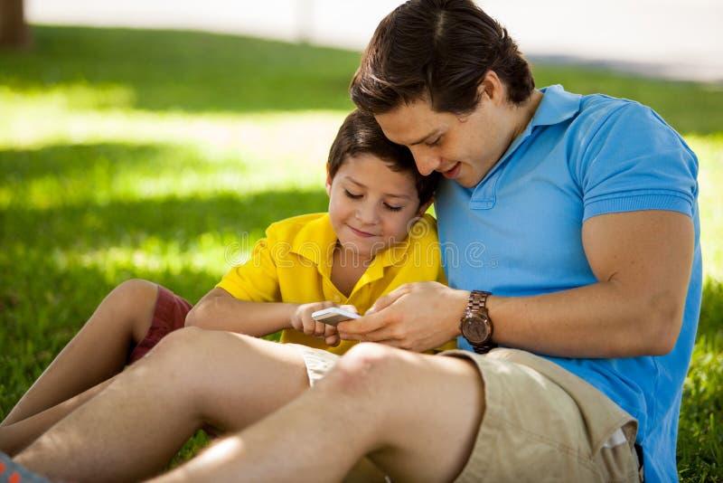 Vader en zoon met een celtelefoon stock afbeeldingen