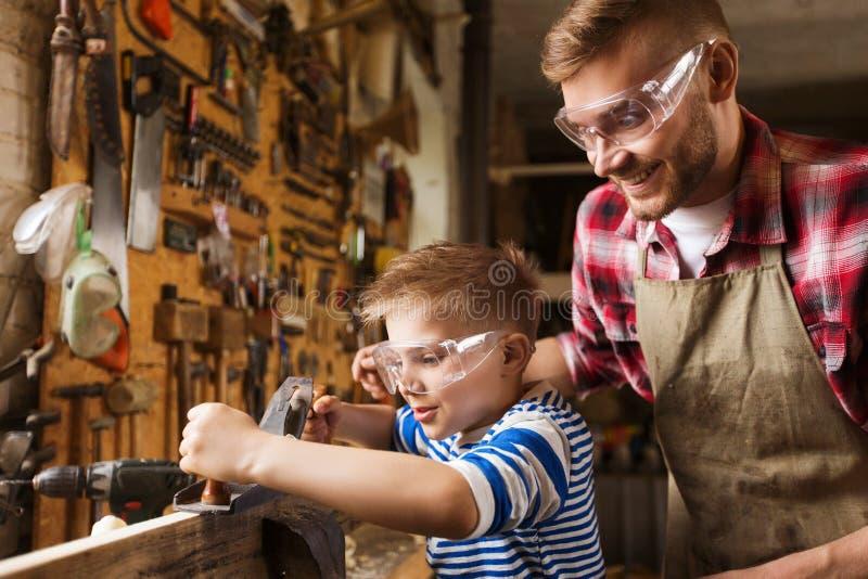 Vader en zoon met vliegtuig het scheren hout op workshop royalty-vrije stock afbeelding