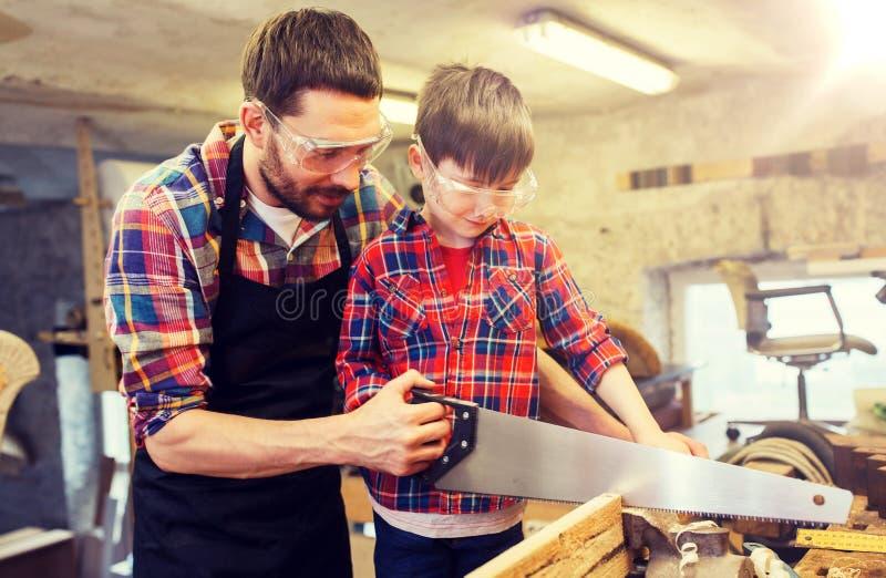 Vader en zoon met zaag die op workshop werken royalty-vrije stock afbeelding