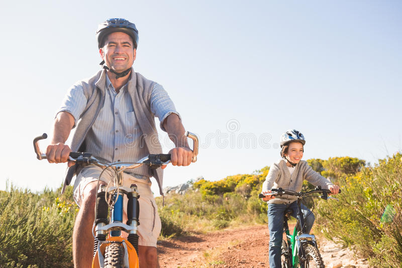 Vader en zoon op een fietsrit stock afbeeldingen