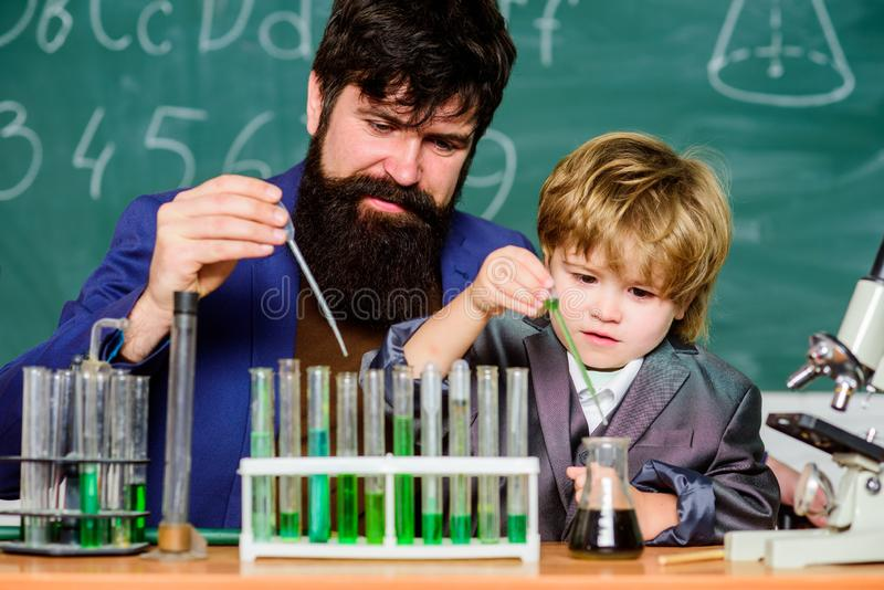 Vader en zoon op school biotechnoloy onderzoekconcept Terug naar School Het verklaren van biologie aan kind Gebaarde mens royalty-vrije stock afbeeldingen