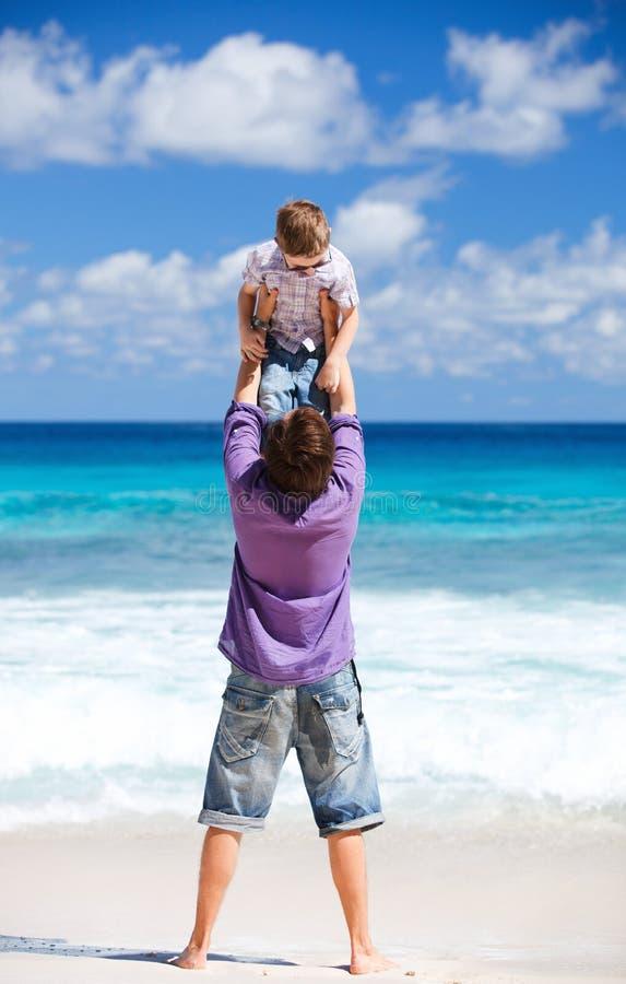 Vader en zoon op strandvakantie stock foto