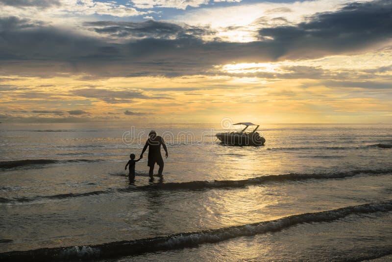Vader en zoon op zonsondergang op overzees royalty-vrije stock foto's