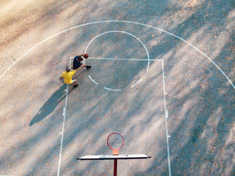 Vader en zoon spelen basketbal in het park stock fotografie